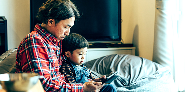 Man and child looking at tablet.